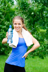 Smiling woman showing water bottle after workout