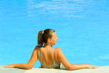 Female beauty relaxing in the swimming pool