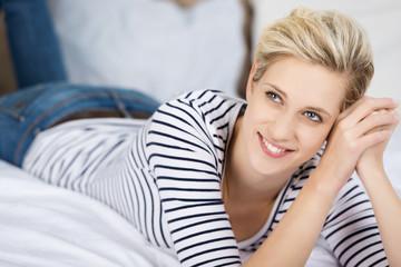 lächelnde blonde frau liegt auf dem bett