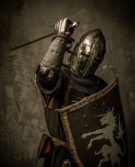 Aluminium Prints Knights Medieval knight with sword and shield against stone wall