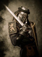Foto op Canvas Ridders Medieval knight with sword and shield against stone wall