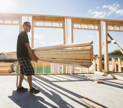 Caucasian man carrying lumber on construction site