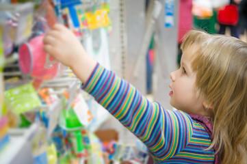 Adorable girl select toys on shelves in supermarket
