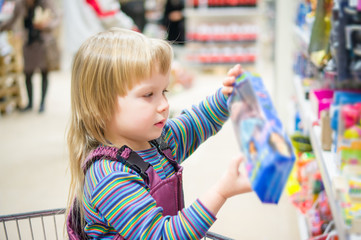Adorable girl select toys on shelves in supermarket