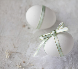White easter eggs with mint ribbons and white feathers