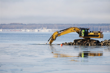 bulldozer doing dredging works in icy sea
