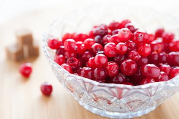 cranberries in a transparent bowl and refined sugar