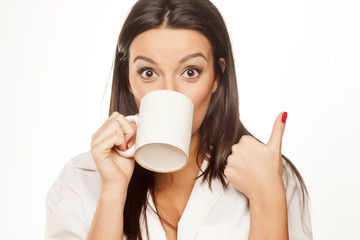surprised beautiful girl drinking tea and shows thumb