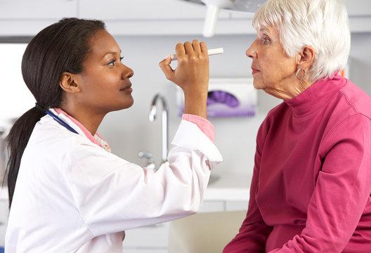 Doctor Examining Senior Female Patient's Eyes