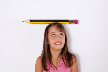 Little girl with a giant pencil over her head