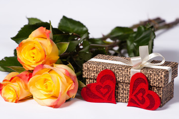 Bouquet of roses with a gift and two hearts