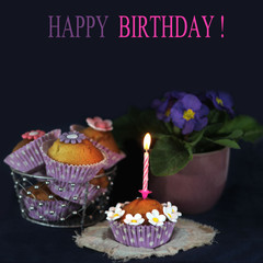 Delicious cupcakes with candle and flowers decoration