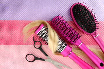 Comb brushes, hair and cutting shears, on bright background