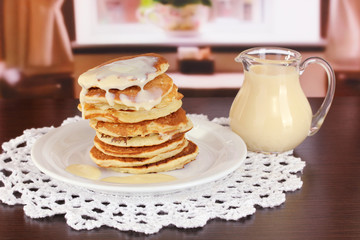 Sweet pancakes on plate with condensed milk on table in room