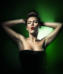 hot beautiful woman with red lips in dark green light