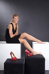 Hübsche Frau mit roten Schuhen lacht