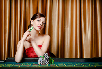Portrait of female gambler sitting at the casino table