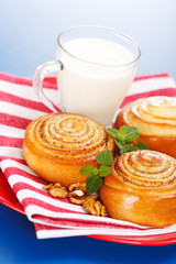 Three cinnamon rolls and jug of milk on red plate