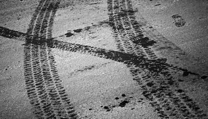 Tire tracks and footstep on the asphalt urban road
