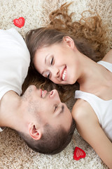 young couple lying on the carpet