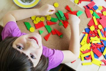 Obraz Preschool girl playing with puzzle - fototapety do salonu