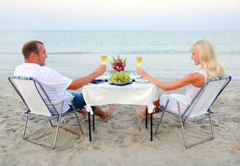 A young couple share a romantic dinner with candles and wine gla