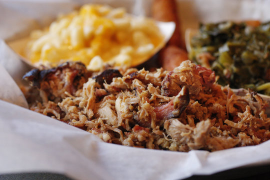 A serving of pulled pork with side dishes