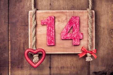 Fourteen valentine card, heart hanging on wooden wall