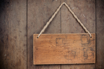 Wooden signboard with rope hanging on grunge wall background