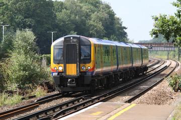 UK commuter train passing station platform