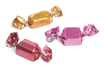 Three wrapped candies or sweets on a white background.