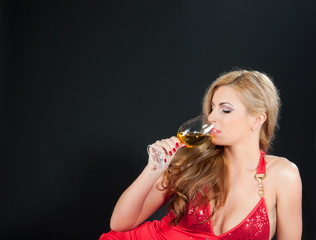 Sexy blonde woman in red dress with  glass of wine