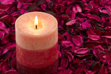 Candle on rose petals