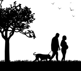 Pregnant woman and her husband walking with his dog