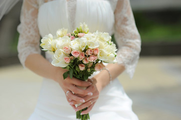 bride holding white roses bouquet in park