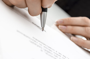 Female hand signing a contract