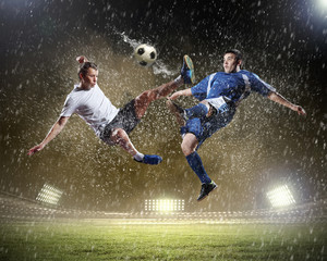 Fotobehang voetbal two football players striking the ball