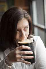 Young Woman with Beautiful Brown Eyes Drinking a Pint of Stout
