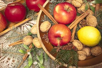 Xmas basket with apple, vlanuts, needles and cinnamon
