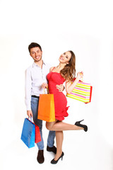 Happy young couple with shopping bags isolated on white bacgkrou