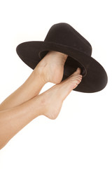 Woman feet cowboy hat on toes