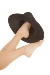 Woman feet cowboy hat on one foot.