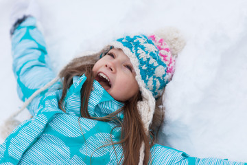Young girl playing and doing snow angel
