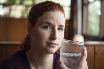 Young Woman with Beautiful Auburn Hair Drinking Water