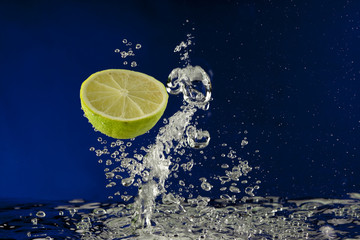 Fruit lime splash in water with bubbles against blue background