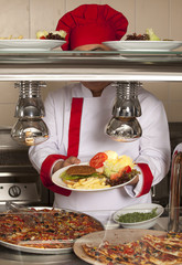 chef standing behind burger and pizza station
