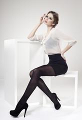 beautiful woman with long sexy legs dressed elegant - studio