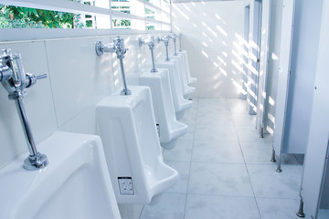 modern restroom interior with urinal row .