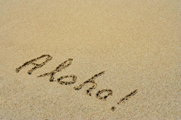 Aloha handwritten in sand on a beach