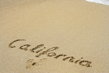 Conceptual handwritten text California in sand